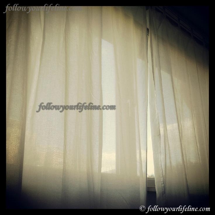 Blick aus dem Fenster durch halbtransparente Vorhänge